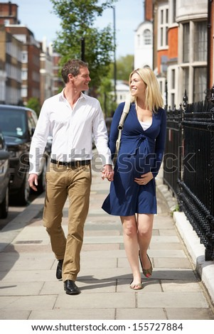 Couple With Pregnant Wife Walking Along Urban Sidewalk