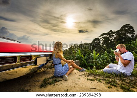 Couple with retro car on vacation - stock photo