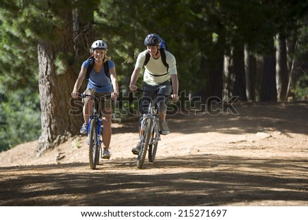Couple, with rucksacks and cycling helmets, mountain biking along woodland trail, smiling, front view