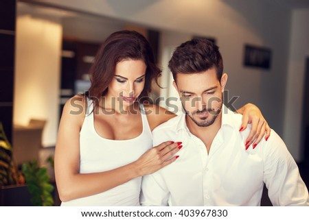Couple with sad upset man at home, woman embrace - stock photo