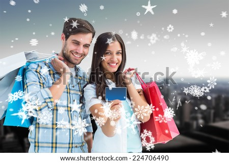 Couple with shopping bags and credit card against high angle view of city skyline - stock photo