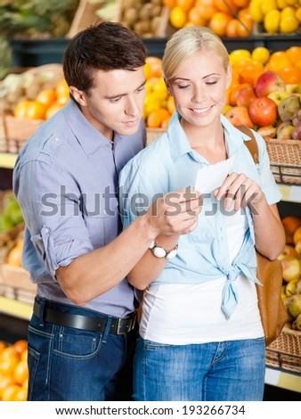 Couple with shopping list against the heaps of fruits decides what to buy