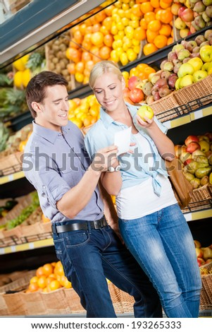 Couple with shopping list against the piles of fruits decides what to buy