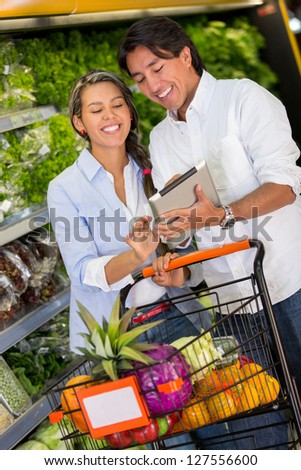Couple with shopping list on a tablet computer at the supermarket - stock photo