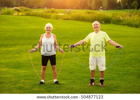 Couple with skipping ropes outdoor. Smiling elderly woman and man. Health of lungs and heart. Count your jumps.