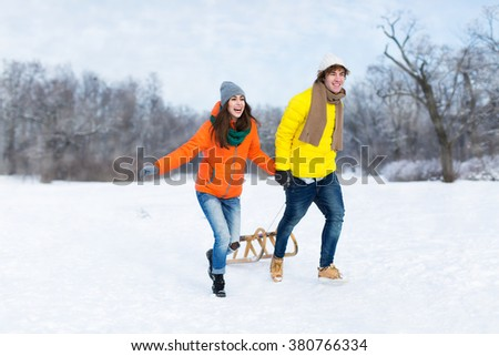 Couple with sled in snow - stock photo