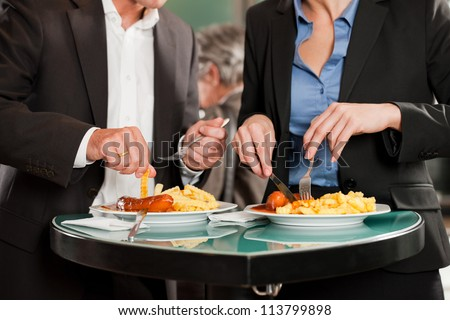 Couple with snack for lunch - sausage and fries - stock photo