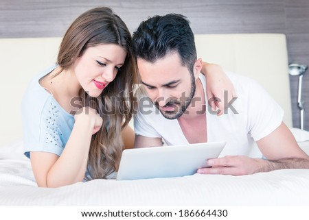 Couple with tablet computers in their bedroom  - stock - stock photo