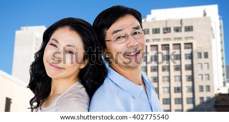 Couple with their backs to each other against low angle view of city buildings