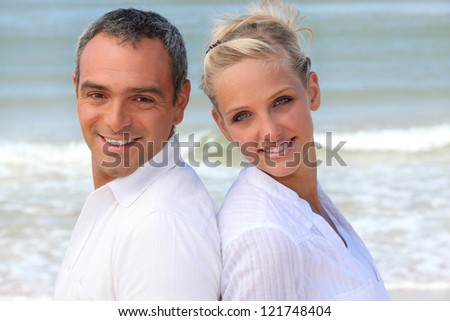 Couple with their backs to the sea - stock photo