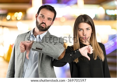 Couple with their thumbs down on unfocused background