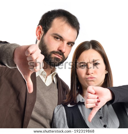 Couple with their thumbs down over white background  - stock photo