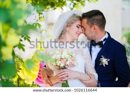 couple with their wedding bouquet posing in the park
