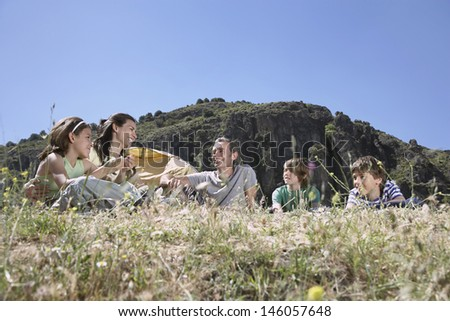 Couple with three children camping on mountain top - stock photo