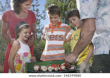 Couple with three children grilling in garden