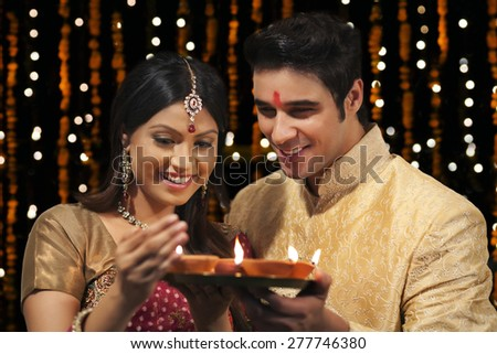 Couple with tray of diyas - stock photo