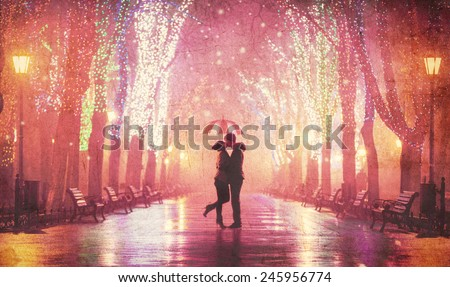 Couple with umbrella kissing at night alley. - stock photo