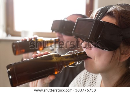 couple with virtual reality glasses is drinking beer