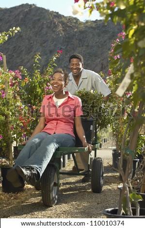 Couple with wheelbarrow at a botanical garden - stock photo