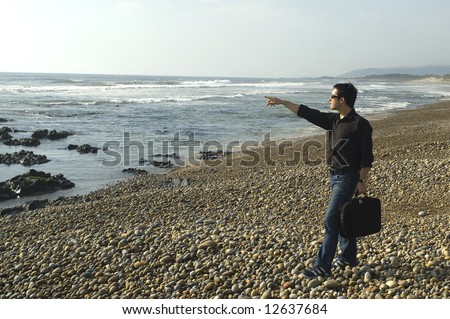 couple with workbook, pointing to the sea ... - stock photo