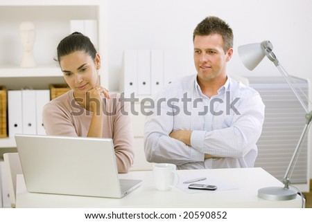 Couple working on laptop computer at home office, happy, smiling. - stock photo