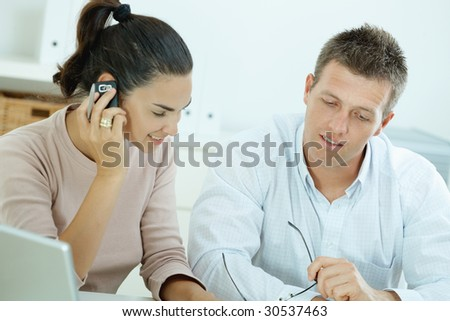 Couple working on laptop computer at home office, happy, smiling. Woman calling on mobile phone. - stock photo