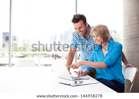 Couple working on laptop in office - stock photo