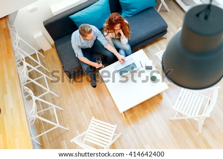 Couple working together in beautiful living room with laptop on desk - stock photo