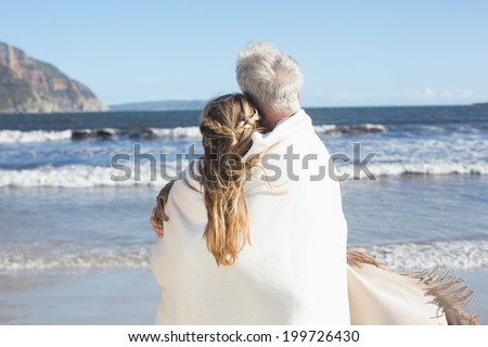 Couple wrapped up in blanket on the beach looking out to sea on a sunny day - stock photo