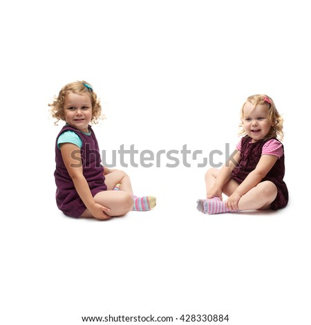 Couple young little girls sisters with curly hair in purple dress sitting over isolated white background - stock photo