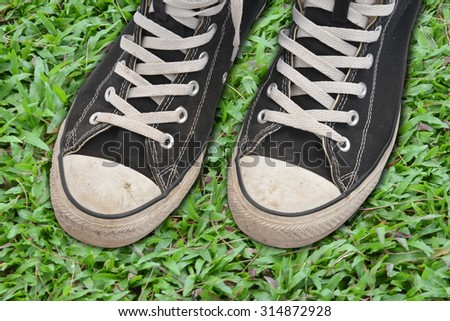 Couple youth sneakers, black and white sneakers, shoes on the green grass,  - stock photo