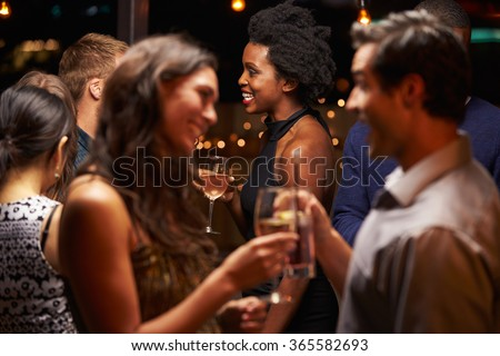 Couples Chatting And Drinking At Evening Party