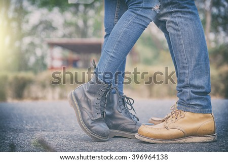 Couples Couple kissing outdoors - Lovers on a romantic date, kiss her man - Close up on shoes. - stock photo