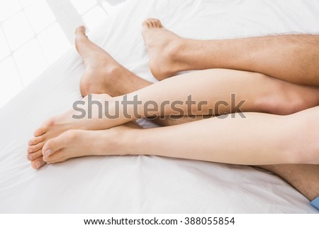 couples feet cuddling on bed in bedroom - stock photo