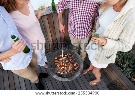 Couples having a barbeque skewer kebabs outdoors - stock photo