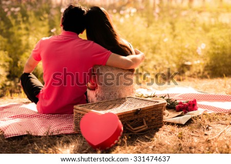 Couples hugging  time together picnic at the park the evening.