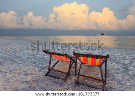 couples of chairs beach and yatching boat at far in sea