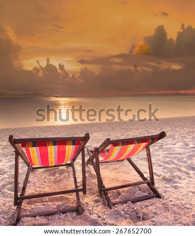 couples of wood chairs beach at sea side and parachute ship playing over sun set sky