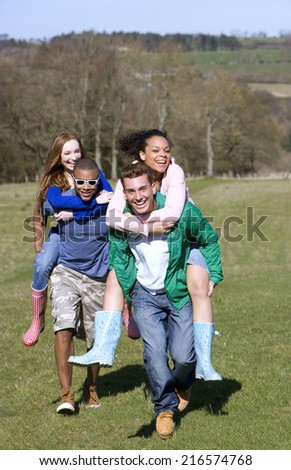 Couples piggybacking in field - stock photo