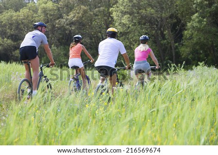 Couples riding bicycles through rural field