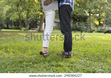 Couples standing on grass on a sunny day