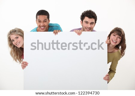 Couples stood with advertising board - stock photo