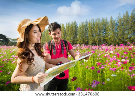 Couples traveling to Viewing Map Cosmos flowers in the garden - stock photo