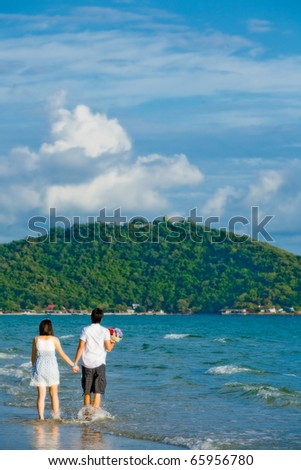 couples walking by hand in hand along the beach with gentle ripple - stock photo