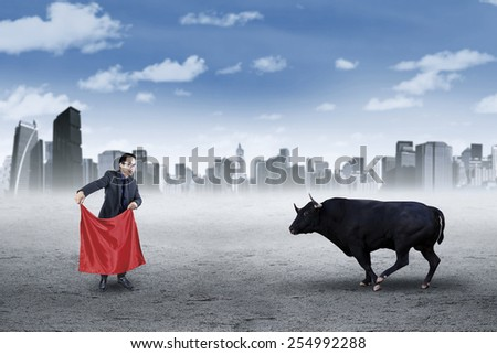 Courage young businessman or stock broker with a mad bull, symbolizing business challenge or bull market - stock photo