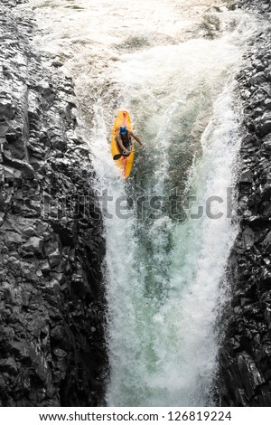 Courageous kayaker in a vertical diving position - stock photo