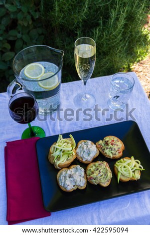 Courgette salad, guacamole and aubergine dip on bread. Cicchetti from Venice Italy, similar to bruschetta or tapas.  Served outside in evening light with iced water, sparkling and red wine. - stock photo