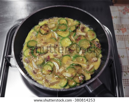 Courgettes and mushrooms omelette vegetarian food in a frying pad on gas cooker