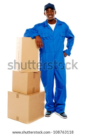 Courier boy standing beside boxes against white background, resting hand on them - stock photo