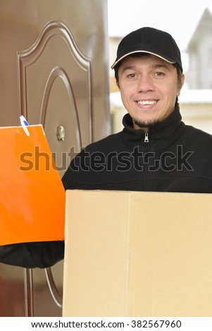 Courier Delivering a Package to entrance - stock photo